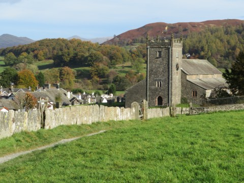 Slate slab wall with the church and village of Hawkshead and a back drop of hills, Cumbria, UK